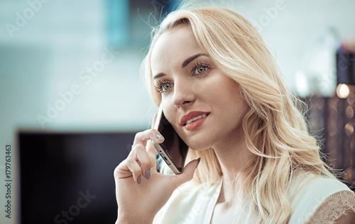 Plexiglas Konrad B. Closeup portrait of a pretty blonde using a smartphone