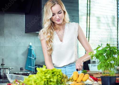 Plexiglas Konrad B. Blonde woman preparing a dinner dish
