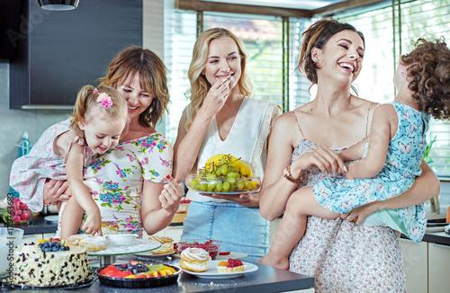 Plexiglas Konrad B. Cheerful women eating cakes and sweets with their children