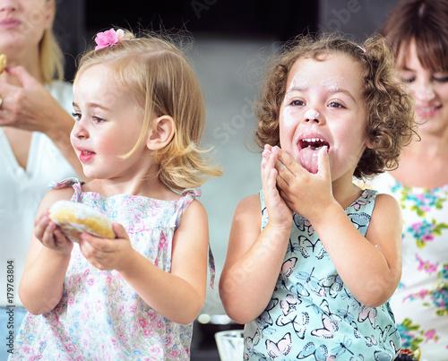 Plexiglas Konrad B. Two cute girls eating sweet doughnuts