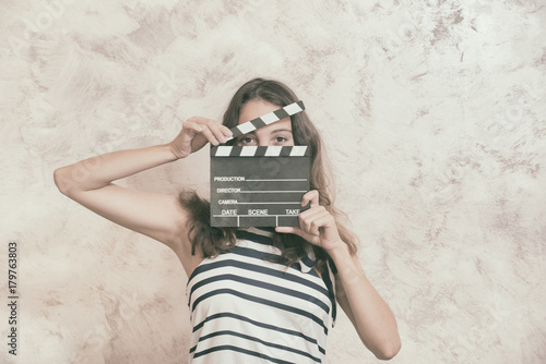 Woman with movie clapper board over face audition concept Poster