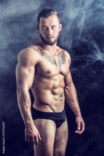 Muscular young man standing and looking to a side, shirtless, wearing briefs, showing chiselled torso, abs and pecs