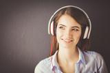 Woman listening music in headphones on windowsill background - 179768610