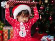 Santa baby girl opening her Christmas gift