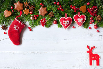 Christmas background with green fir branches, sock, reindeer, hearts, cookies and red berries