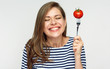 Happy woman holding fork with tomato.