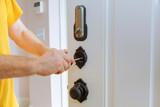 Closeup of a professional locksmith installing or repairing a new deadbolt lock - 179789413