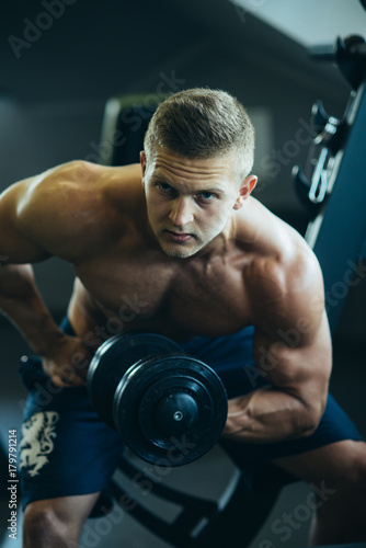 Bodybuilder man build hand muscles with dumbbell in gym