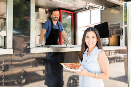 Woman buying pizza from a food truck