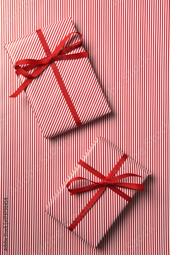 Two Christmas presents wrapped with red striped paper Poster