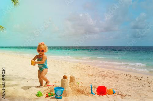 cute little girl play with sand, building castle on beach