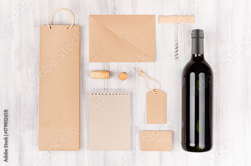 Corporate identity template for wine industry,  blank brown kraft packaging, stationery, merchandise set with bottle red wine on soft white wood background.