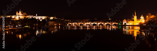 Prague castle and Charles bridge night panorama with city light with reflection Poster