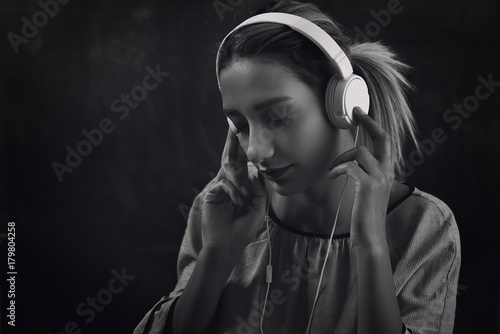 Fototapeta Portrait woman listening to music on headphones