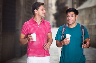 Male tourists walking with coffee