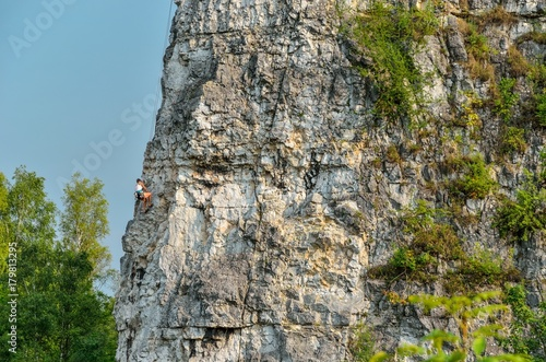 Beautiful rocky summer landscape. Climber on the rocks of Twardowski at the lagoon of Zakrzowek in Krakow, Poland.