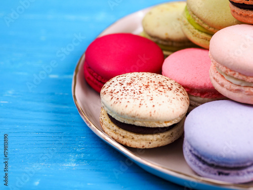 Fotobehang Macarons Traditional brightly colored French macaroons on a hand-made plate, set on a blue wooden board, close-up view, selective focus