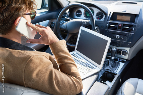 Rear view of unrecognizable successful man using laptop and speaking by phone sitting inside of expensive car, copy space