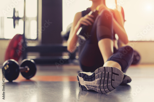 Woman exercise workout in gym fitness breaking relax holding protein