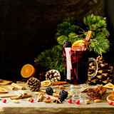 glass of hot mulled wine for the new year with ingredients for cooking, nuts and Christmas decorations - 179816602