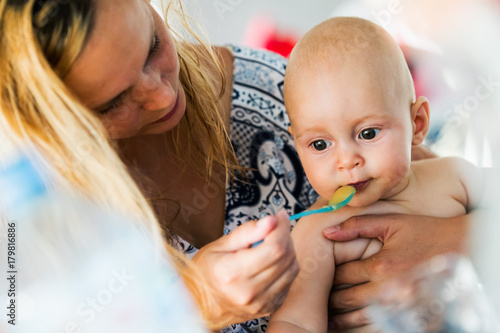 Fridge magnet Portrait of mother feeding her baby with spoon