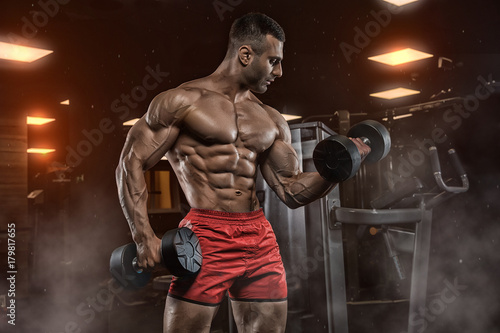 Poster man in gym. Muscular bodybuilder guy doing exercises with barbell. Strong person. Sports background. Young athlete ready for weight lifting training.