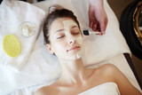 Top view portrait of beautiful young woman in SPA, lying on massage table with eyes closed while cosmetologist applying face mask to her face - 179826810