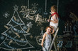 Children decorate the Christmas tree. Brother and sister draw a Christmas song on the wall