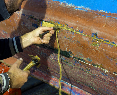 Fotobehang Schip The sailor repairs his fishing boat by clogging the cracks in the timber with a cotton rope