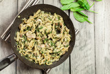 Tagliatelle pasta with spinach and mushrooms on a pan. - 179841028