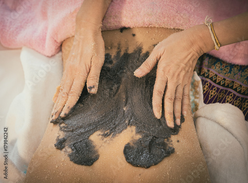Fotobehang Spa Spa Therapist is applying Charcoal coffee scrub on to a woman back