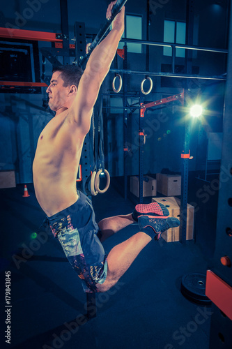 Concept: power, strength, healthy lifestyle, sport. Powerful attractive muscular man at CrossFit gym