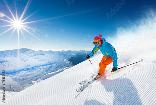 Skier skiing downhill in high mountains - 179854495