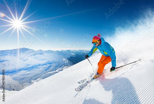 Leinwanddruck Bild Skier skiing downhill in high mountains