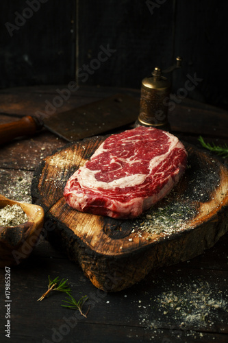 Papiers peints Steakhouse Raw fresh ribeye steak with salt, spices, and rosemary