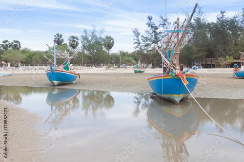 Fotobehang Schip Wooden fishing boat on the low tide beach.