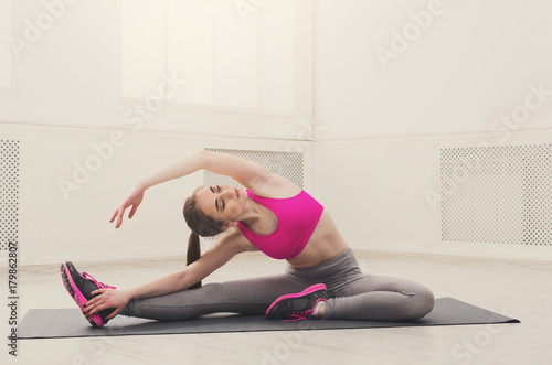 Poster Fitness woman stretching at white background indoors