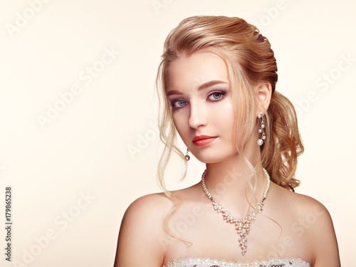 Fotobehang Kapsalon Blonde Girl with Long and shiny Curly Hair. Beautiful Model Woman with Curly Hairstyle. Care and Beauty Hair products. Perfect Make-Up and Jewelry