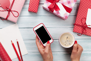 Female holding smartphone and wrapping christmas gifts