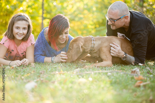 Family lying on the grass in the park with their dog Poster