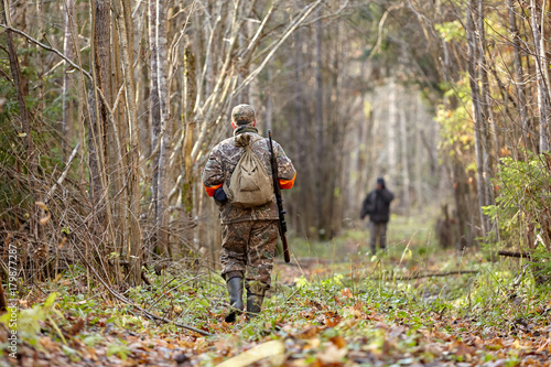 Fotobehang Jacht Hunter in camouflage clothes with hunting rifle during a winter hunting