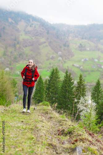 Fotobehang Olijf Young smiling tourist woman with a backpack in the mountains enjoying the scenery
