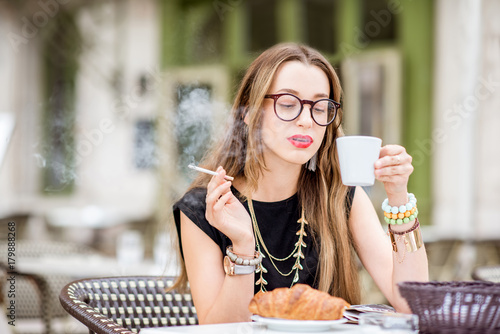 Young woman smoking a cigarette while having a breakfast outdoors at the typical Poster