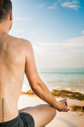Poster Handsome man doing yoga at cliff with blue sea background