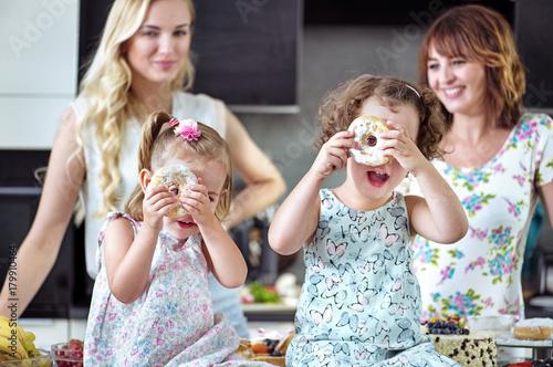 Plexiglas Konrad B. Pretty women eating sweets with their children