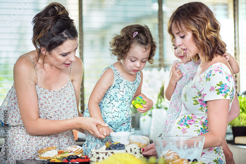 Foto op Canvas Artist KB Young mothers making a cake with their daughters