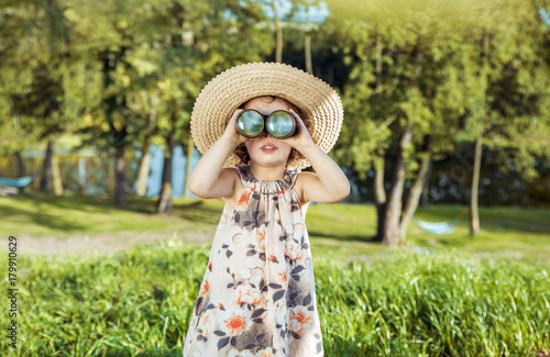 Plexiglas Konrad B. Portrait of a cheerful, little girl looking through the binoculars