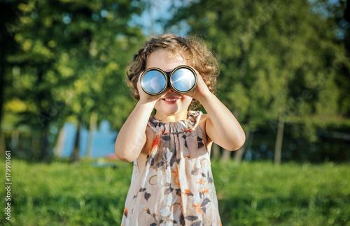 Plexiglas Konrad B. Portrait of a cheerful girl looking through the binoculars