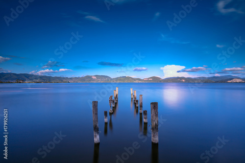 Fotobehang Pier Wooden pier or jetty remains on a blue lake sunset and sky reflection on water. Versilia Tuscany, Italy