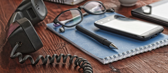 modern office . a handset a notepad and glasses lie on the desktop. a modern workplace © gannamartysheva
